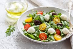 Fresh summer salad with arugula, yellow and red cherry tomatoes, Kalamata olives and mozzarella. Selective focus stock photo