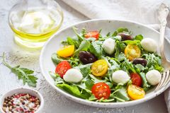 Fresh summer salad with arugula, yellow and red cherry tomatoes, Kalamata olives and mozzarella. Selective focus stock images