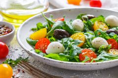 Fresh summer salad with arugula, yellow and red cherry tomatoes, Kalamata olives and mozzarella. With spices in a white plate . Selective focus royalty free stock images