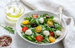 Fresh summer salad with arugula, yellow and red cherry tomatoes, Kalamata olives and mozzarella. Selective focus royalty free stock photo