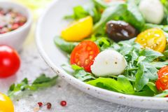 Fresh summer salad with arugula, yellow and red cherry tomatoes, Kalamata olives and mozzarella. With spices in a white plate . Selective focus stock photos
