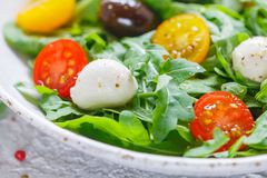 Fresh summer salad with arugula, yellow and red cherry tomatoes, Kalamata olives and mozzarella. With spices in a white plate . Selective focus royalty free stock photos