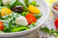 Fresh summer salad with arugula, yellow and red cherry tomatoes, Kalamata olives and mozzarella. With spices in a white plate . Selective focus royalty free stock image