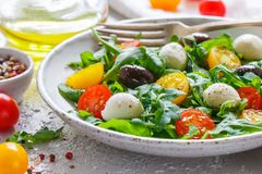 Fresh summer salad with arugula, yellow and red cherry tomatoes, Kalamata olives and mozzarella. With spices in a white plate . Selective focus stock image