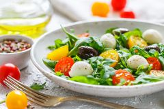 Fresh summer salad with arugula, yellow and red cherry tomatoes, Kalamata olives and mozzarella. With spices in a white plate . Selective focus royalty free stock photography