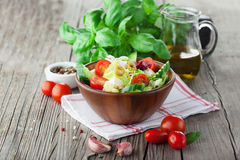 Fresh summer salad. With cherry tomatoes, spinach, arugula, romaine and lettuce on dark wooden background, selective focus stock image