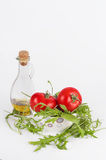 Fresh summer salad, isolated: red ripe tomatoes, rucola salad and olive oi Royalty Free Stock Photography
