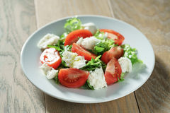 Fresh summer salad with tomatoes, rucola, frillis and mozzarella in plate on wood table Royalty Free Stock Image