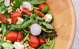 Fresh summer salad. Top view of fresh salad with arugula, cherry tomatoes, mozzarella, radish, olive oil,pine nuts presented in wooden bowl Stock Images