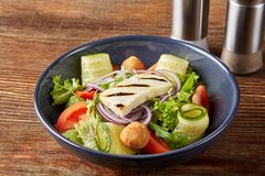 Fresh summer vegetarian salad with tomatoes, spinach and roasted tofu cheese in a plate on wooden background. royalty free stock images