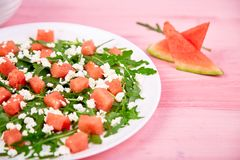 Fresh summer watermelon salad with feta cheese and arugula. On pink table background. Vegan food. Diet, Vegetarian.Copy space royalty free stock images