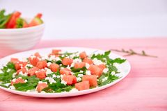 Fresh summer watermelon salad with feta cheese and arugula. On pink table background. Vegan food. Diet, Vegetarian. Copy space royalty free stock photos