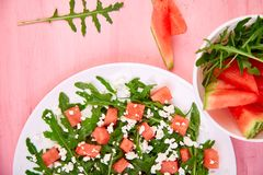 Fresh summer watermelon salad with feta cheese and arugula. On pink table background. Vegan food. Diet, Vegetarian. Top view. Flat lay. Copy space stock image