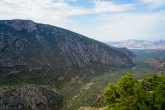 Fresh surrounding view of Parnassus mountain slope valley, green olive groves through Ionian sea with bright sky background. Delphi, Greece royalty free stock images