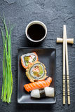 Fresh sushi, dark ceramic and chopstick. On black rock Stock Image