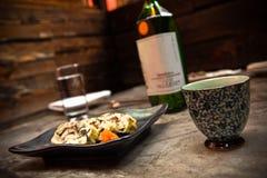 Fresh Sushi Platter. On black plate with sake bottle Stock Photo