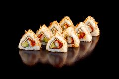 Fresh sushi rolls with eel and avocado in shavings of fish on a black background. Royalty Free Stock Photo