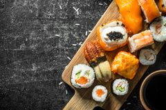 Fresh sushi and rolls with soy sauce. On dark rustic background royalty free stock image