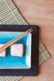 Fresh sushi salmon cream cheese parcels on plate with chopsticks Royalty Free Stock Images