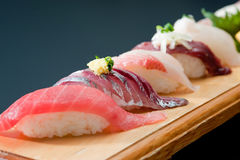 Fresh sushi with salmon, rice, squid, wasabi on wooden tray Royalty Free Stock Photography