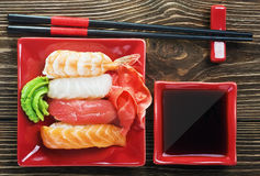 Fresh sushi served in a red plate with black chopsticks Royalty Free Stock Images