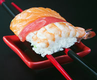 Fresh sushi served in a red plate with black stripes Royalty Free Stock Photos