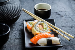 Fresh sushi served in with tea. Closeup of fresh sushi served in with tea on black rock Stock Photo