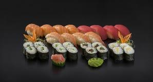 Fresh Sushi set. Nigiri and Hosomaki sushi rolls. Isolation on a black background Royalty Free Stock Photography