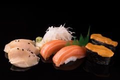 Fresh Sushi set. Sushi and sashimi served on a black reflective surface. Isolated on a black. Fresh and delicious sushi set served on a black reflective surface stock photography