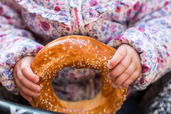 Fresh, sweet bagel in young children's hands Royalty Free Stock Photography