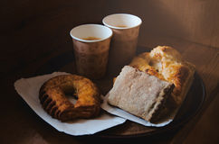 Fresh sweet bakery bread, two kraft cups of black coffee on a paper tray, wooden background. Coffee break concept Royalty Free Stock Photos