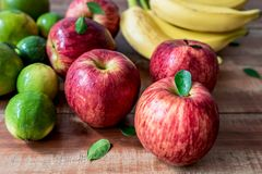 Colorful fresh bananas, lemons, oranges and apples on wooden background royalty free stock photography