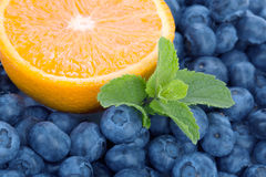 Fresh and sweet blueberries, mint and half of juicy lemon as a background. Nutritious lemon and organic bilberries. Stock Photo