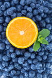 Fresh and sweet blueberries, mint and half of juicy orange as a background. Nutritious orange in a center of bilberries. Stock Images