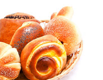 Fresh sweet buns and rolls with poppy and cream in the basket Stock Photography