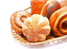 Fresh sweet buns and rolls with poppy and cream in the basket Stock Photos