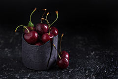 Fresh sweet cherries in black cup Stock Image
