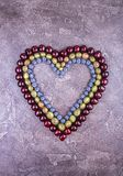 Fresh sweet cherries, blueberry and goosberry in heart shape over on concrete gray background. Top view royalty free stock photo