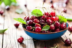 Fresh sweet cherries bowl with leaves in water drops on wooden b. Ackground, top view stock images
