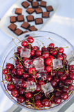Fresh sweet cherries on dessert table. Fresh sweet cherries in a glass cold plate with ice cubes on a dessert table royalty free stock image