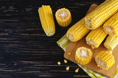 Fresh sweet corn on cobs. At black rustic wooden table Royalty Free Stock Images