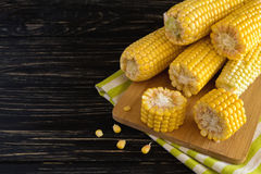 Fresh sweet corn on cobs. At black rustic wooden table Stock Image