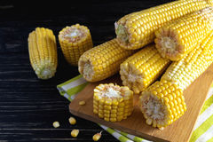 Fresh sweet corn on cobs. At black rustic wooden table Royalty Free Stock Photography