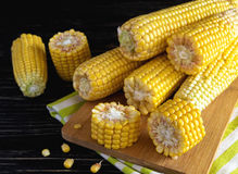 Fresh sweet corn on cobs. At black rustic wooden table Royalty Free Stock Photos