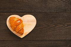 Fresh sweet croissant on the brown wooden table royalty free stock photo