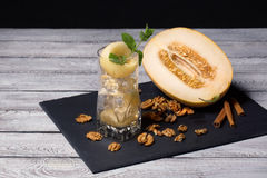 A fresh sweet melon, walnuts and a glass of ice, mint and honeydew on a wooden background. Natural ingredients. A cut cantaloupe. stock images