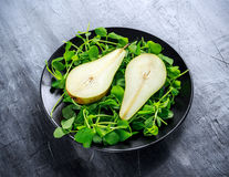 Fresh sweet Pears with green salad on black plate Royalty Free Stock Photos