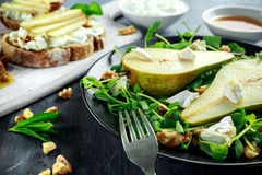 Fresh sweet Pears salad and bruschetta with cottage cheese, walnut on white board. Royalty Free Stock Photos