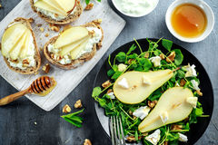 Fresh sweet Pears salad and bruschetta with cottage cheese, walnut on white board. Royalty Free Stock Photo