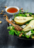 Fresh sweet Pears salad with walnuts, honey and white soft cheese on black plate Royalty Free Stock Photo